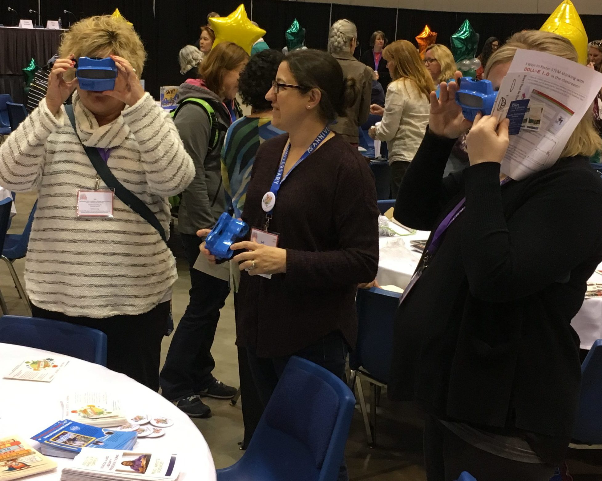 Educators check out simulated canine vision with Jodi Wheeler-Toppen (center). They hold blue viewmasters to their eyes and peer at slides that are mounted on wheels and inserted into the viewmaster.