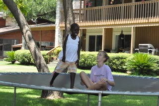 Rebeka Uwitonze runs circles around Meredith's daughter on their trampoline.
